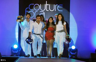 Abhishek Awasthi L and Akruti Mistry walk the ramp with designer Aarti Vijay Gupta C during the latters show Couture For A Cause at ITC Maratha in Mumbai