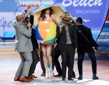 Singer Bruno Mars center performs while a model walks the runway.
