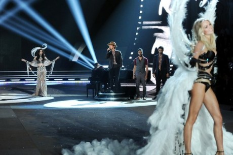 Singer Bruno Mars center performs while a models walk the runway.